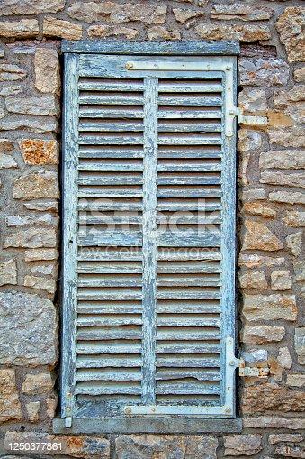 Cobblestones frame a woody window