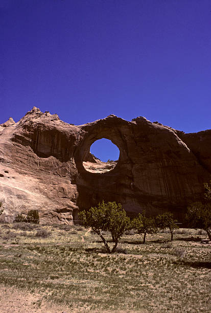 Window Rock, Navajo Reservation Window Rock formation on the Navajo Reservation in Arizona. Lots of copy space in the deep blue sky. Dry brush and sand in foreground. hearkencreative stock pictures, royalty-free photos & images