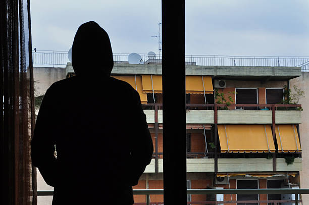 window shadow Man looking at city buildings through window. creepy stalker stock pictures, royalty-free photos & images