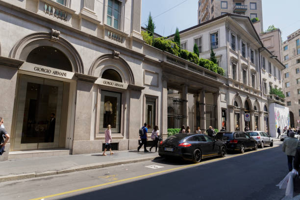Window shopping crowd outside Giorgio Armani & Louis Vuitton Milano fashion district famous shops & high end exclusive boutiques stock photo