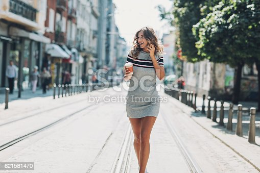 Smiling young woman talking on the phone and walking on the street in downtown area.