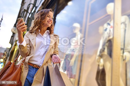 Photo of a young woman shopping in the city while checking her mobile phone and smiling.