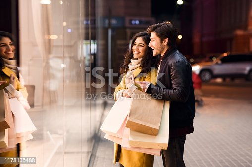 Window shopping. Young couple looking at showcase, walking near city center in the evening, free space