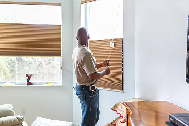 Window treatment installer installs the cord on shades stock photo