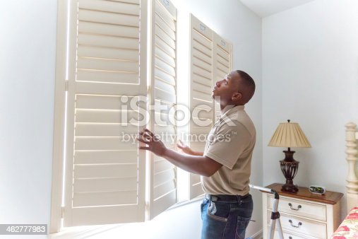 istock Window treatment installer installs wooden shutters 462777983