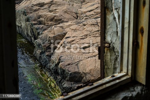 Abstract image of a big rock formation on the Black Sea shore seen through a broken window.