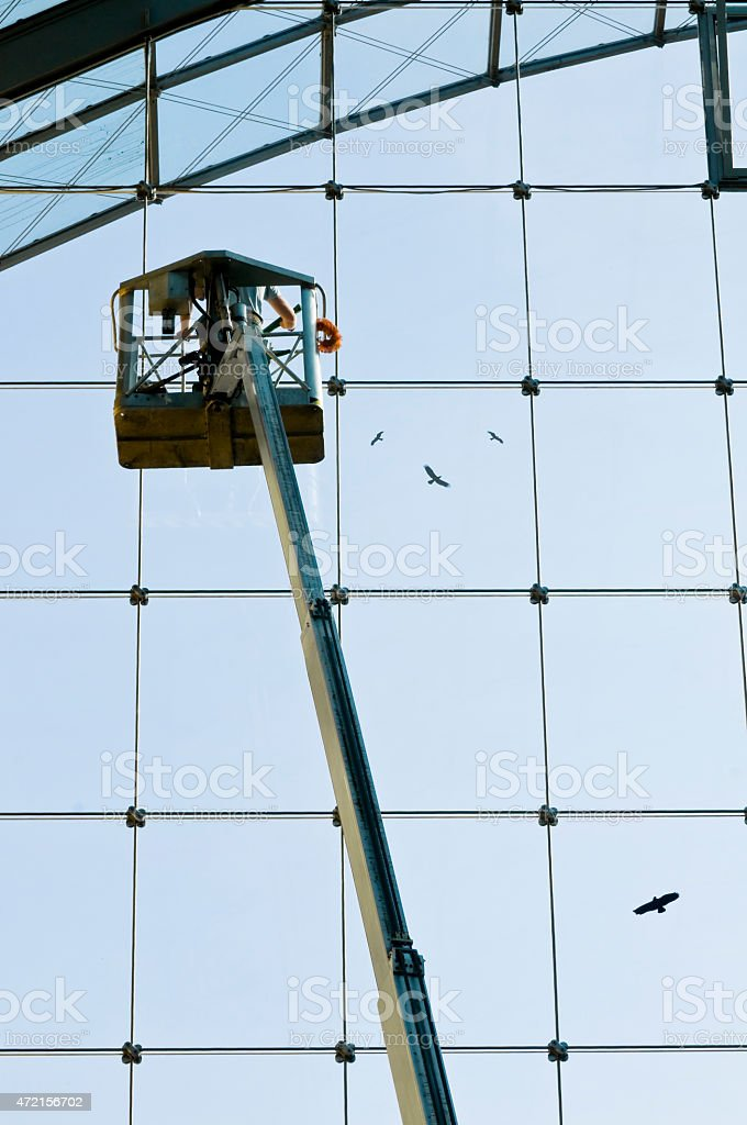 Window washer on a hydraulic hoist at work stock photo