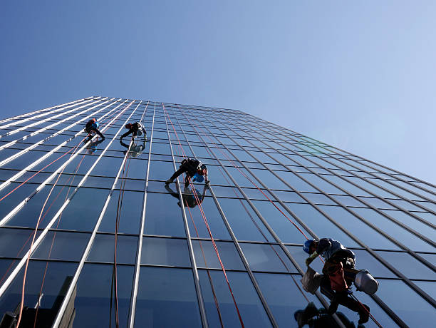 Window washers Cleaning windows on the side of a high rise building high up stock pictures, royalty-free photos & images