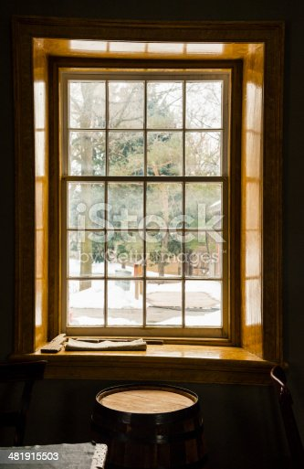 An  old fashioned wooden window frame with view of winter through the window panes and an old wooden barrow in front of the window.