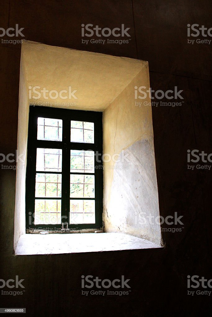 window with bars Small window high in the wall with a lattice, as a symbol of restrictions on freedom of Anxiety Stock Photo