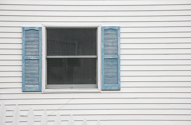 Window with blue shutters and exterior wall stock photo