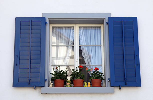 window with blue shutters and flower pots, Switzerland. stock photo