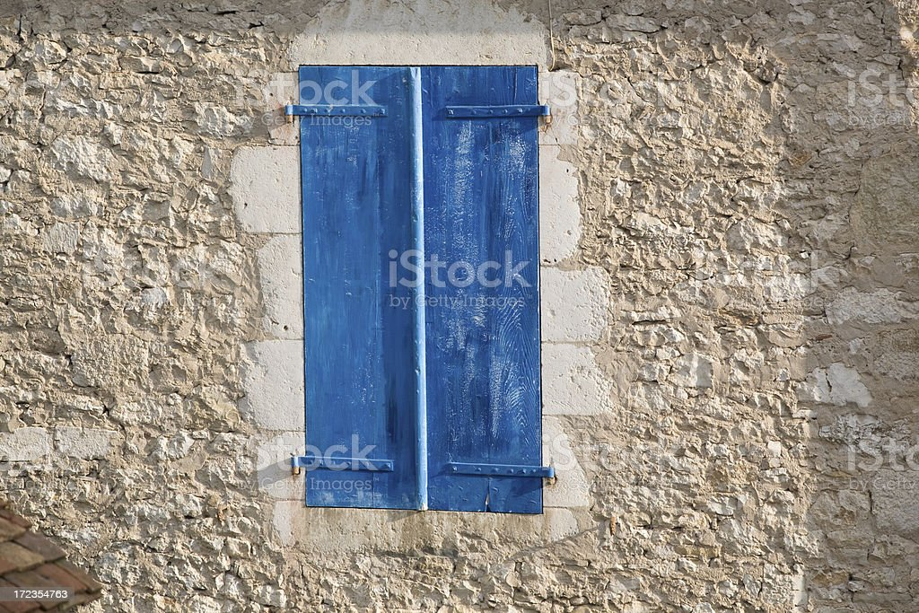 Window with blue shutters in a stone wall royalty-free stock photo