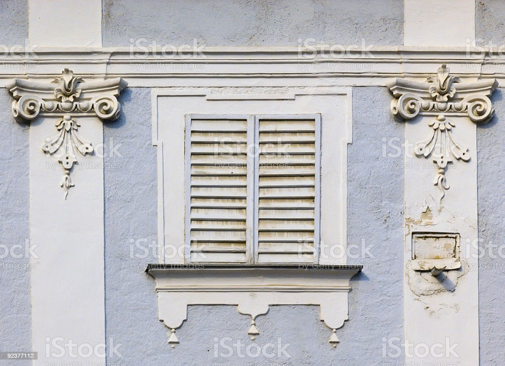 Window with closed shutters in an old facade royalty-free stock photo