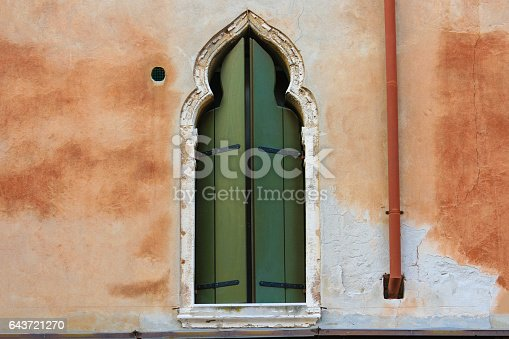 Close-up of the facade of a Medieval House with red stucco exterior in Venice, Italy. In the center is a window with closed green shutters.