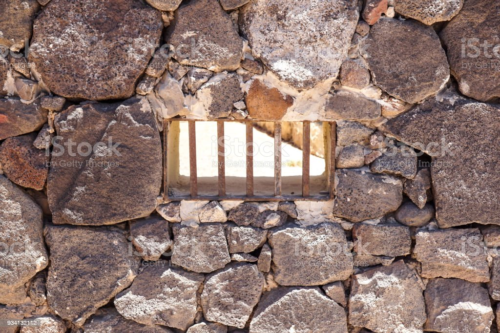 Window with iron bars on old facade with bricks - foto stock