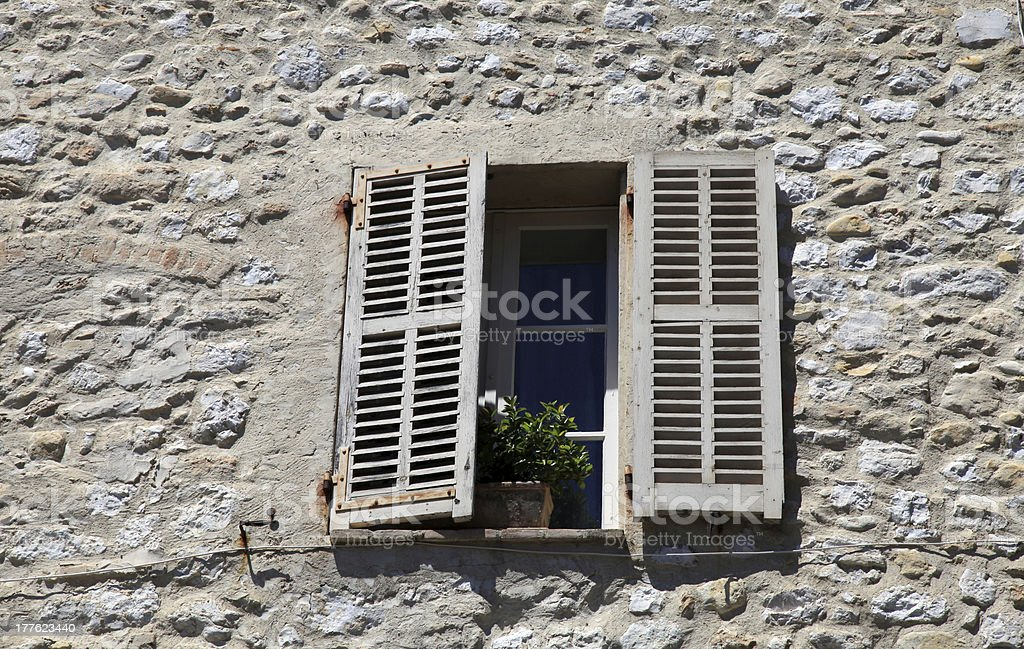window with old wood shutters in rural house, Provence, France. royalty-free stock photo