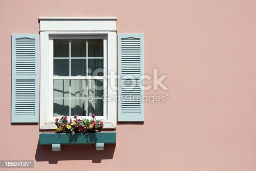 An old sash window with a blue window box and shutters on a pink background. Artificial flowers are in the window box.