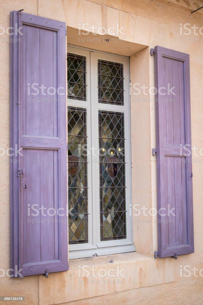Fenster mit lila Fensterläden in einer alten Fassade im mediterranen Stil. – Foto
