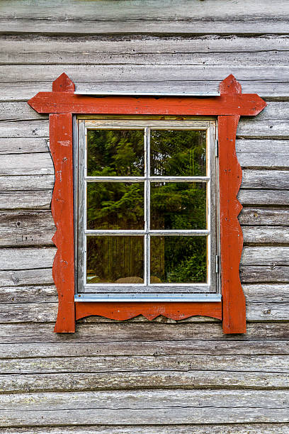 Window with red frames on log house wall, traditional style. stock photo