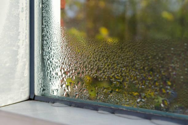 window with water drops closeup, inside, selective focus - влажный стоковые фото и изображения