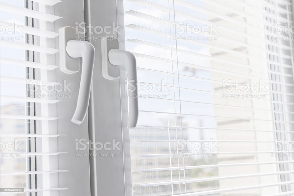 Window with white jalousie, close up stock photo