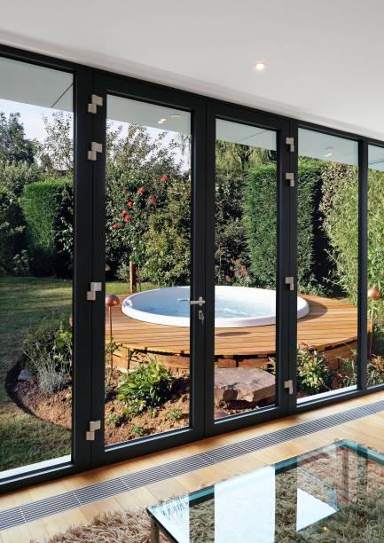 Fenster und Türen gegen üppigen Laubgarten und Blasenpool – Foto