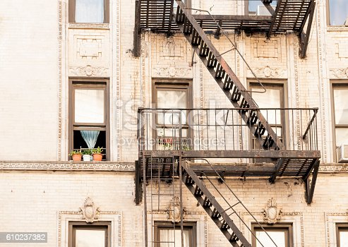 This is a horizontal color photograph of the exterior of a multi story, residential, New York City apartment building in the Lower East Side neighborhood of Manhattan. Brown fire escapes go up the exterior cream colored facade. One window is open on a warm autumn day. Photographed with a Nikon D800 DSLR camera.