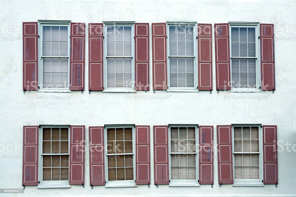 Windows and shutters askew in 18th building royalty-free stock photo