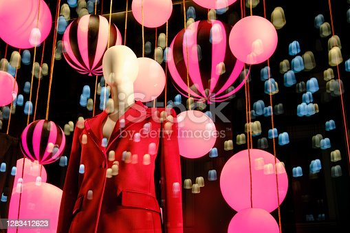 Windows clothing stores with balloons and lanterns on the eve of Christmas and new year celebrations. Woman mannequin in a suit in a clothing store