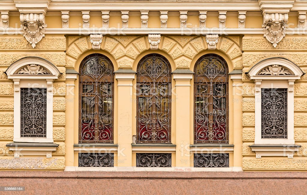 Windows in a row with wrought grate on facade stock photo