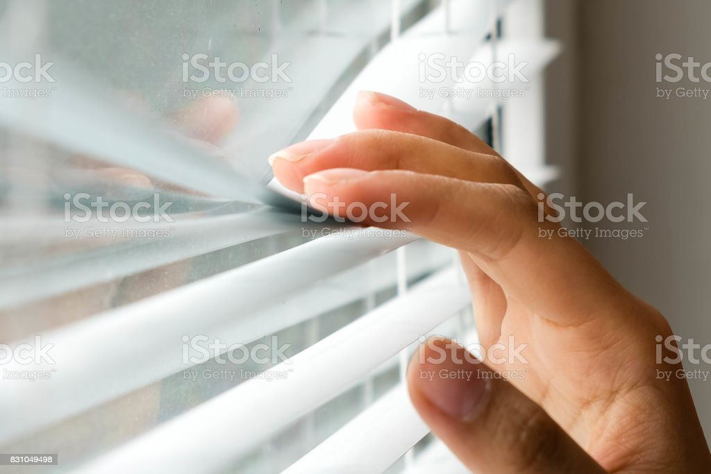 Windows jalousie. woman peeking through window blinds. Male hand separating slats of venetian blinds with a finger to see through with soft light stock photo
