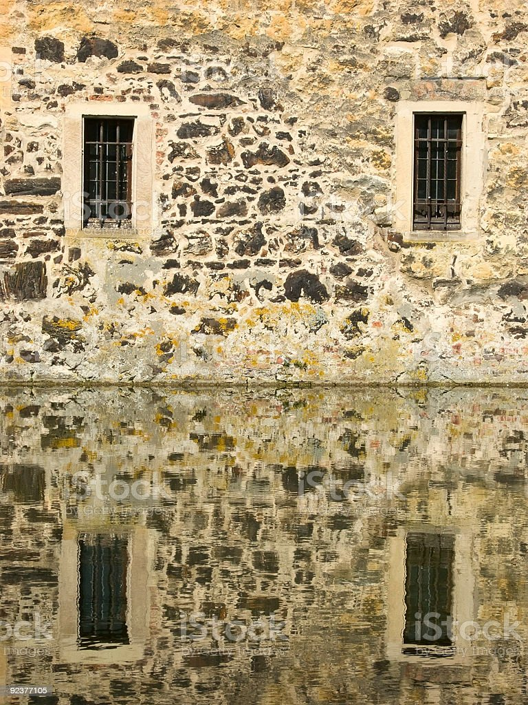 Windows of a castle reflecting in water royalty-free stock photo