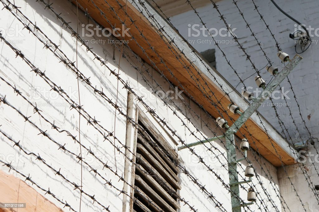 Windows of prison cells behind a fence with barbed wire under high voltage, close-up stock photo