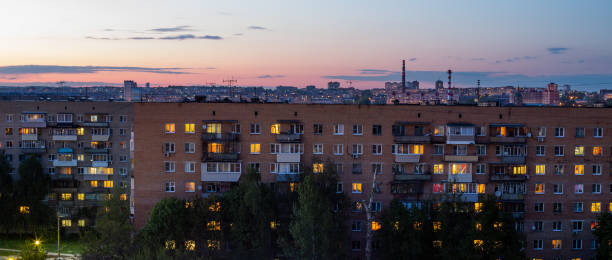 Windows, roofs and facade of an mass brick apartment building in Eastern Europe. Panoramic shot. stock photo