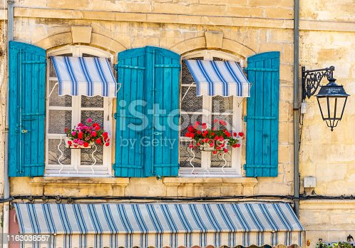 Arles, Provence-Alps-Cote d'Azur, France - June 2, 2019: View of windows with blue shutters in the historic city center.