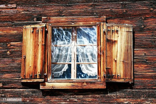 Windows with curtains and shutters on an old wooden house