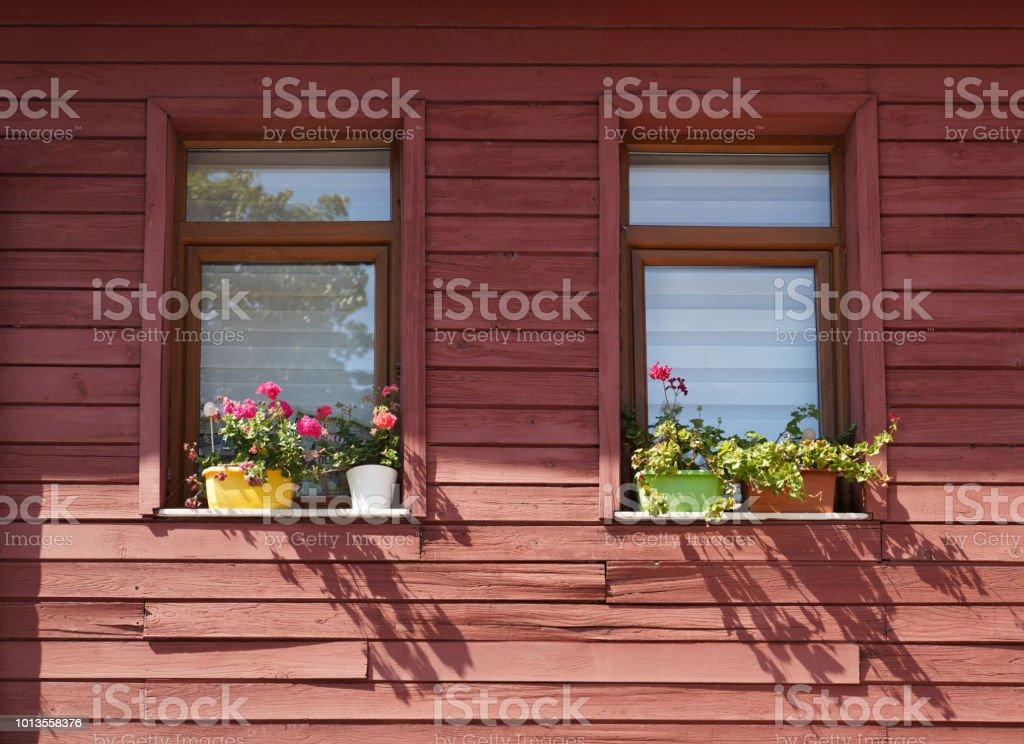 Pencere çiçekler bir kahverengi ahşap cephe geleneksel bir ev renkli. stok fotoğrafı