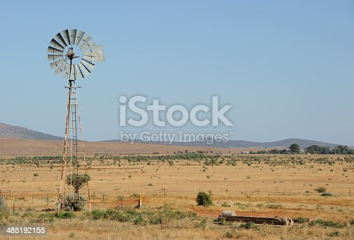 A wind-powered waterpump in the South Australian Outback near the town of Hawker, farm in the distance