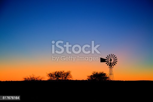 A typical farm setting in the morning with a windpump and the sun about to rise in the background. Slight movement in the blades of the windpump from the wind blowing it on.