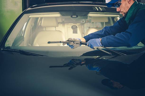 Windscreen Wiper Replacement Windscreen Wiper Replacement by Professional Auto Service Technician windshield wiper stock pictures, royalty-free photos & images