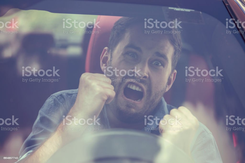 Windshield view of an angry driver man. Negative human emotions face expression stock photo