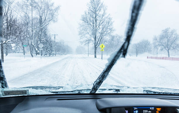 Windshield Wipers Clearing Car Windshield During Blizzard Snow Storm Windshield wipers are working hard to clear heavy, blowing snow which is coming down hard on this suburban Rochester, New York residential neighborhood street during a mid-February winter blizzard snow storm. Deep tire track ridges and valleys from earlier cars on the frozen and already extremely slippery road surface make driving and especially steering the car more difficult and dangerous. windshield wiper stock pictures, royalty-free photos & images