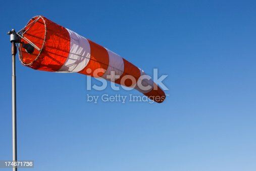 A windsock isolated against a clear blue sky.