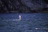 A lone windsurfer at dawn near the city of Lecco, on Como Lake.