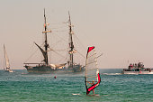 Elba Island, Tuscany, Italy - August 23, 2011: A windsurfer, an ancient sailing ship and some boats in the gulf of Marina di Campo, Elba Island.