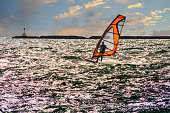 Backlit by the afternoon sun and using the brisk winds off the ocean,  a windsurfer skims over the silvery surface of Hyannis harbor with the Hyannis port breakwater in the background.