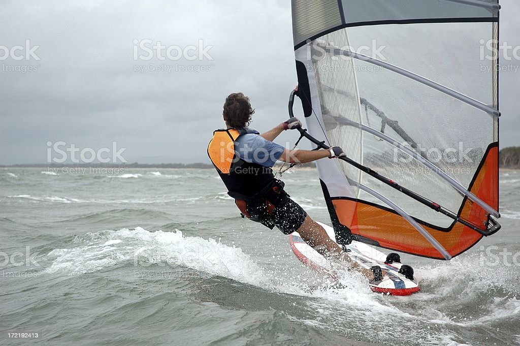 Windsurfer cruising by rear view royalty-free stock photo