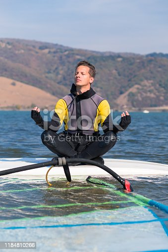 istock Windsurfer doing yoga while sitting on surfboard. Sport and relaxation concept. 1184810266