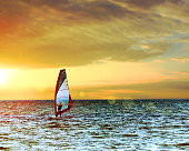 Windsurfer in the sea with a scenic sunset sky. Toned, lens sun flare. Active sport vacation concept.